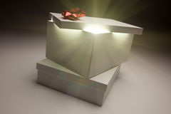 Red Bow Gift Box Lid Showing Very Bright Contents. Gift Box with Red Bow Lid Revealing Very Bright Contents on a Gradated Background Royalty Free Stock Photo