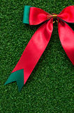 Red Bow on green grass. Christmas Stock Photo