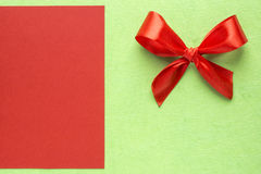 Red bow on green with red background Royalty Free Stock Images