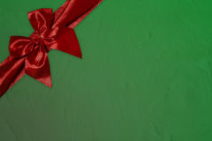 Red bow on green stone textured Royalty Free Stock Photos