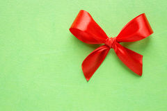Red bow on green texture Royalty Free Stock Photo