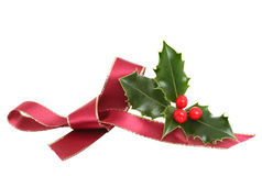 Red bow and holly. Red ribbon bow and a sprig of fresh holly with ripe berries isolated against white royalty free stock photo