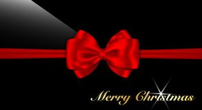 Red bow and Merry Christmas words on glossy black. Royalty Free Stock Photos