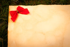 Red bow on old paper Royalty Free Stock Images