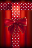 Red bow and patterned ribbon on red background Stock Photography