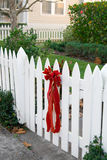Red Bow on Picket Fence. Big red velvet bow on a white picket fence welcomes visitors stock images