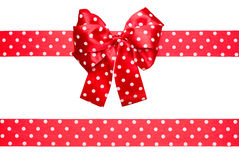 Red bow and ribbon with white polka dots made from silk. Isolated stock photos