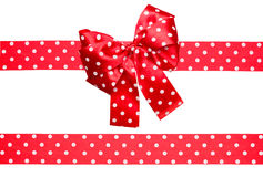 Red bow and ribbon with white polka dots made from silk Stock Image