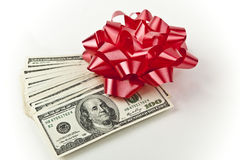 Red bow with stack of money. Off center stack of hundred dollar bills with red bow on white background room for text lower right Royalty Free Stock Photo