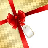 Red bow with tag on gold background Stock Image