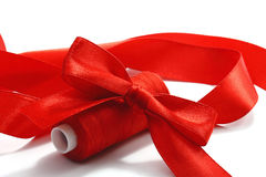 Red bow and threads. Red bow, tape and the coil red threads on a white background Royalty Free Stock Images