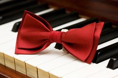 Red bow tie. On the piano keys Stock Photos