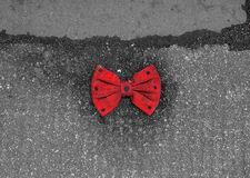 Red bow tie with black dots lying on the pavement. Of a street Stock Photo