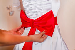 Red bow tie on the bride's dress Royalty Free Stock Images