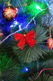 Red bow and toy on a Christmas tree. Red bow and toy on a green Christmas tree Royalty Free Stock Image