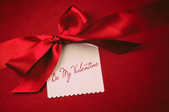 Red bow and white card for gift on velvet Stock Image