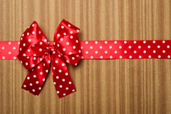Red bow on wood background Royalty Free Stock Photo