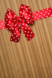 Red bow on wood background Royalty Free Stock Photography