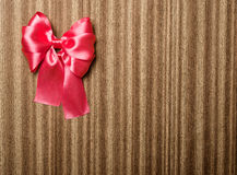 Red bow on wooden background Royalty Free Stock Images