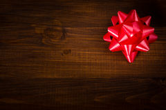 Red bow on wooden brown planks Stock Image