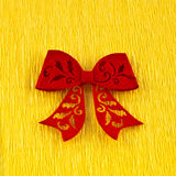 Red bow on yellow paper Royalty Free Stock Images