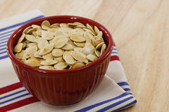 Red bowl brimming with toasted pumpkin seeds Royalty Free Stock Photography