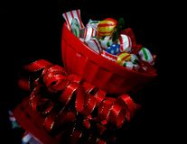 Red bowl with Christmas candy and  ribbon angled Stock Photo