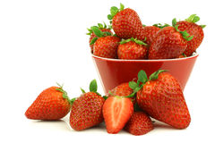 Red bowl full of fresh strawberries and a cut one Royalty Free Stock Photos