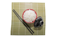 Red bowl of rice with wooden chopsticks and a wood place mat Royalty Free Stock Images