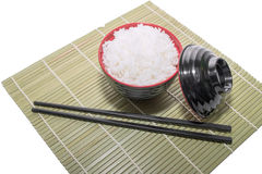 Red bowl of rice with wooden chopsticks and a wood place mat Stock Image