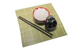 Red bowl of rice with wooden chopsticks and a wood place mat Royalty Free Stock Image