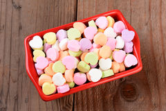 Red Bowl with Valentines Candies. High angle view of a red rectangular candy bowl filled with Valentine's Day Candies. The heart shaped candy is blank and ready royalty free stock images