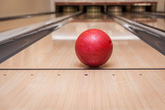 Red bowling ball on the track in the bowling center Stock Image