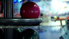Red bowling balls on return machine. Slow motion. Close up bowling balls for play bowling stock footage