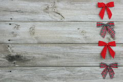 Red bows bordering wood sign. Red plaid bows and red velvet bows bordering wood sign on right Royalty Free Stock Photography