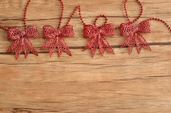 Red bows. Isolated on a wooden background Royalty Free Stock Photos