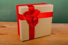 red box for Christmas gifts on a green background, Christmas gifts, red ribbon, red bow royalty free stock image