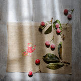 Red box , embroidery and frozen cherries on a wooden gray background Royalty Free Stock Image