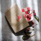 Red box , embroidery and frozen cherries on a wooden gray background Stock Photo
