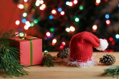 Red box gift with the green bow in the pine branches, red Christmas hat and pine cones on a wooden table next to the Christmas t. Christmas still life: red box Stock Photography