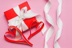 Red box with a gift, tied with a white ribbon, and red homemade paper hearts on a pink background. Symbol of Valentine`s Day stock photos