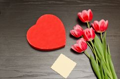 Red box in heart shape, clean card, pink tulips. Black table. top view, space for text.  Royalty Free Stock Images