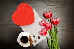 Red box in heart shape, pink tulips, white sheet and a coffee mug. Black table. top view Stock Image