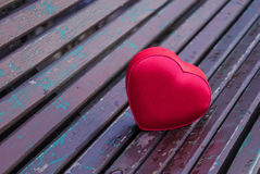 Red box heart shaped on the bench. In park Stock Images
