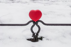Red box heart shaped on the fence. In the winter park Royalty Free Stock Photography