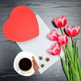 Red box in heart shaped, pink tulips, gray sheet and a coffee mu Stock Photo