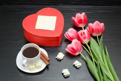 Red box in heart shaped, pink tulips, gray sheet and a coffee mu Royalty Free Stock Images