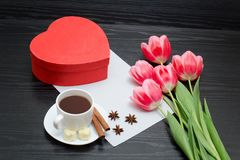 Red box in heart shaped, pink tulips, gray sheet and a coffee mu Royalty Free Stock Image