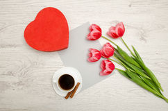 Red box in heart shaped, pink tulips, gray sheet and a coffee mug. Light table Royalty Free Stock Images