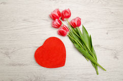Red box heart shaped and pink tulips on a light wooden background. Top view Royalty Free Stock Photo